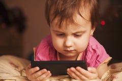 Petite belle fille avec son développement futé de téléphone, educat Photo stock