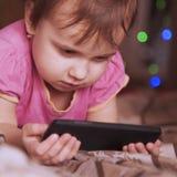 Petite belle fille avec son développement futé de téléphone, educat Image stock