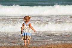 Petite belle fille heureuse se tenant sur la plage image libre de droits