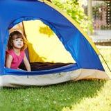 Petite belle fille s'asseyant dans la tente Images stock