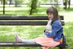 Petite belle fille s'asseyant sur un banc de parc et tenant son fa Photo libre de droits