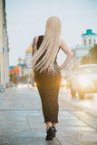 Petite blonde short stature in a big city. Petite blonde short stature in a city Royalty Free Stock Photo