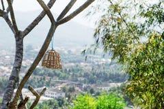Petite cage en bois pour des oiseaux sur un arbre sur une colline de Pho SI sur un fond d'une ville Images libres de droits