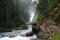 Petite cascade à écriture ligne par ligne en stationnement national de glacier Photo stock