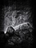 Petite cascade tombant sur des roches Photographie stock libre de droits