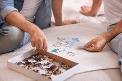 Petite case avec des puzzles se trouvant sur le lit Image libre de droits
