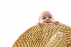 Petite chéri cachée derrière un grand chapeau, verticale Image stock