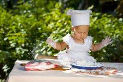 Petite chéri dans le chapeau de cuisinier. Photo stock