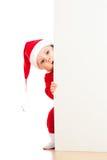 Petite chéri de Santa regardant derrière le bannere de plaquette Photo stock