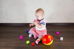 Petite chéri jouant avec des jouets Le petit enfant mâche sur un jouet Image stock