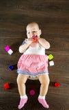 Petite chéri jouant avec des jouets Le petit enfant mâche sur un jouet Images stock
