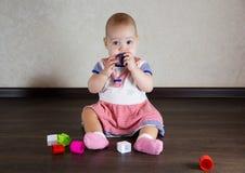 Petite chéri jouant avec des jouets Le petit enfant mâche sur un jouet Photographie stock