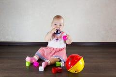 Petite chéri jouant avec des jouets Le petit enfant mâche sur un jouet Images libres de droits