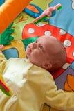 Petite chéri jouant sur le couvre-tapis Photographie stock