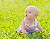 Petite chéri s'asseyant sur l'herbe Photographie stock libre de droits