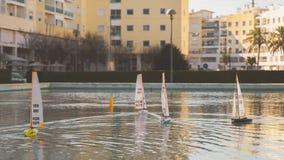 Petite course de bateaux de navigation de jouet Mini bateaux à voile télécommandés d'étang au coucher du soleil image libre de droits