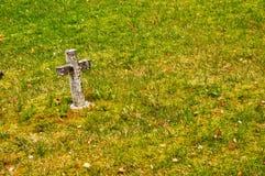 Petite croix en pierre dans l'herbe Image libre de droits