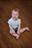 Petite crying baby girl sitting indoor on the wooden floor Stock Image