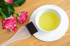Petite cuvette en céramique avec de l'huile rose d'arome Ingrédients pour les cosmétiques faits maison et les soins de la peau na Image stock
