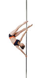 Petite dancer posing upside down on pole Royalty Free Stock Photography