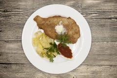 Petite escalope de veau de saucisse avec les pommes de terre et le ketchup bouillis Servi d'un plat blanc de porcelaine sur un fo Images libres de droits