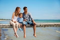 Petite famille de trois par la plage Photos stock
