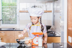 Petite farine de blé asiatique d'émoi de fille faisant la crêpe Photos stock