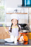 Petite farine de blé asiatique d'émoi de fille faisant la crêpe Photo stock