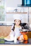 Petite farine de blé asiatique d'émoi de fille faisant la crêpe Photo libre de droits