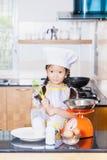 Petite farine de blé asiatique d'émoi de fille faisant la crêpe Photographie stock libre de droits