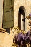 Petite fenêtre avec des fleurs de glycine dans Asolo Photo stock