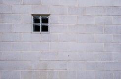 Petite fenêtre carrée dans un grand mur de briques blanc Image stock