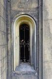 Petite fenêtre de gril dans le mur en pierre Image stock