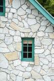 Petite fenêtre en bois dans un cottage en pierre avec l'équilibre et le pignon verts image libre de droits