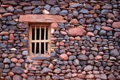 Petite fenêtre en bois dans un mur en pierre antique images stock