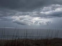 Petite figure sur le rivage au-dessous du ciel menaçant Image stock
