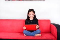 Petite fille à l'aide d'une tablette à la maison Photographie stock libre de droits