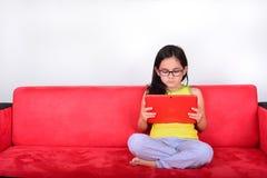 Petite fille à l'aide d'une tablette à la maison Photo libre de droits