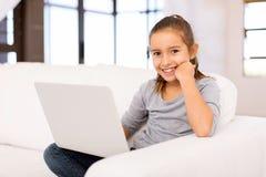 Petite fille à l'aide de l'ordinateur portatif photo stock