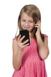 Petite fille à l'aide des téléphones portables Image stock