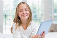 Petite fille à l'aide du PC de comprimé se reposant sur son lit image libre de droits
