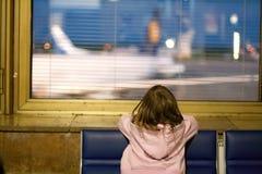 Petite fille à l'hublot dans l'aéroport la nuit. Photographie stock