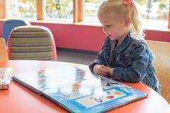 Petite fille à la bibliothèque Images libres de droits
