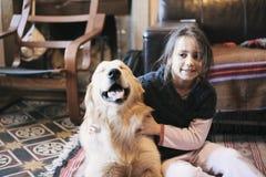 Petite fille à la maison avec son chien de golden retriever Images libres de droits