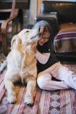 Petite fille à la maison avec son chien de golden retriever Photos stock
