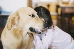 Petite fille à la maison avec son chien de golden retriever Images stock
