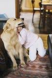 Petite fille à la maison avec son chien de golden retriever Photo libre de droits