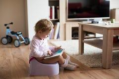 Petite fille à la maison s'asseyant sur le pot jouant avec le comprimé image libre de droits