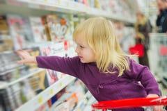 Petite fille à la section de revues dans le supermarché Photographie stock libre de droits