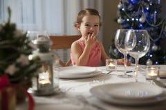 Petite fille à la table de Noël photographie stock libre de droits